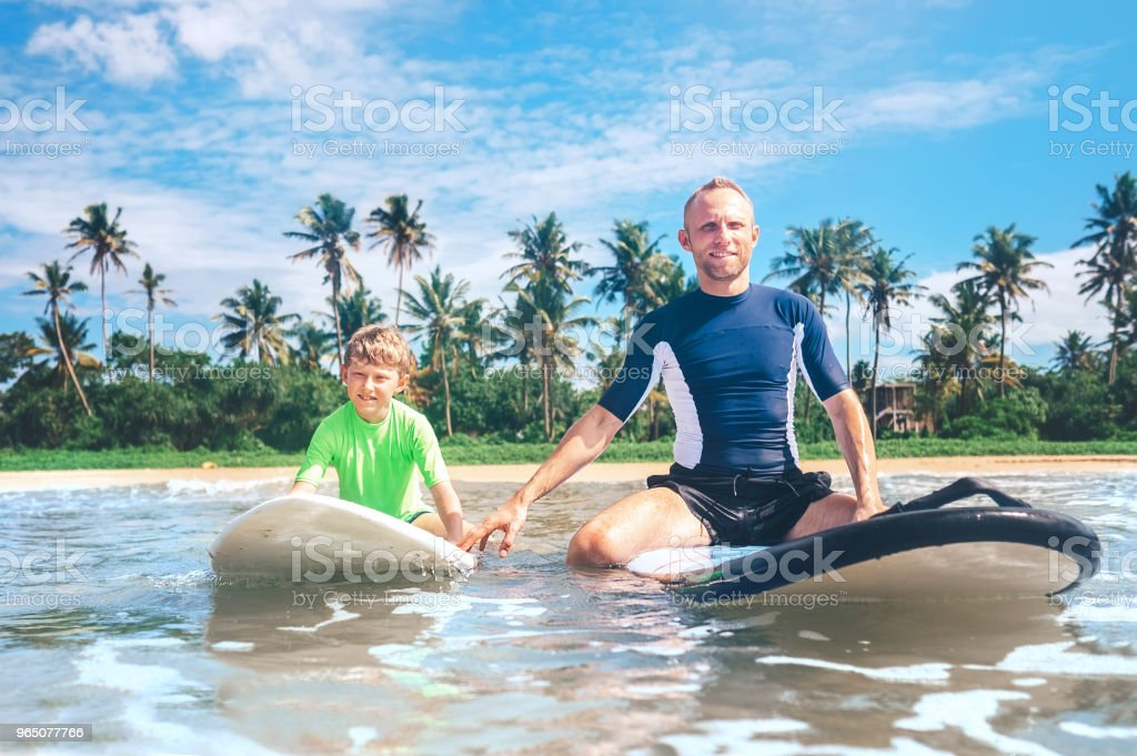 Father and son sit on surfboards. First surfing lessons royalty-free stock photo