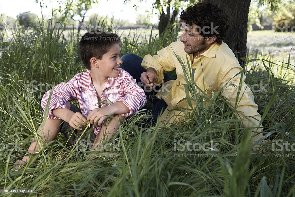 Father and son (8-9) sitting in grass under tree and talking royalty free stockfoto