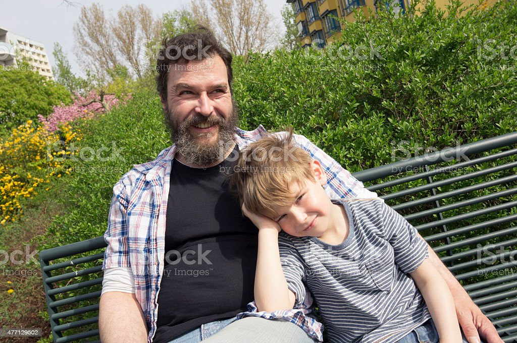Father and son sitting on bench in park, Berlin, Germany stock photo