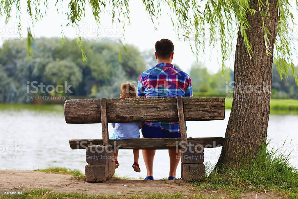 father and son sitting on bench near the lake stock photo