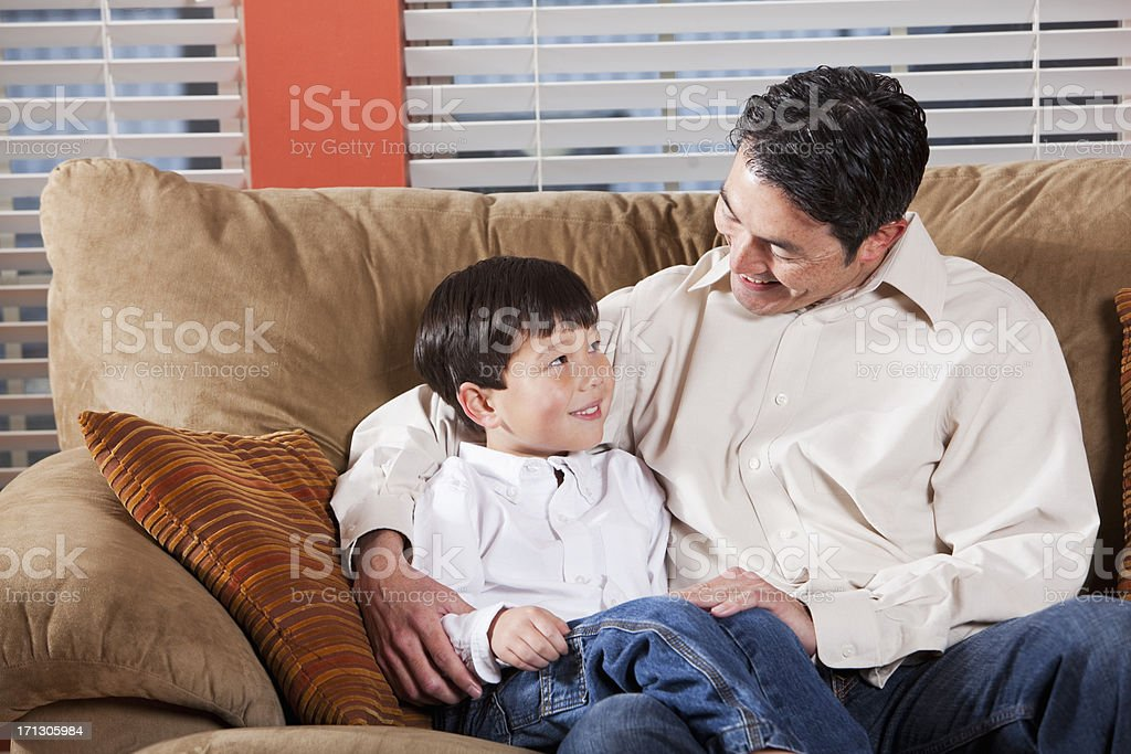 Father and son sitting on couch stock photo