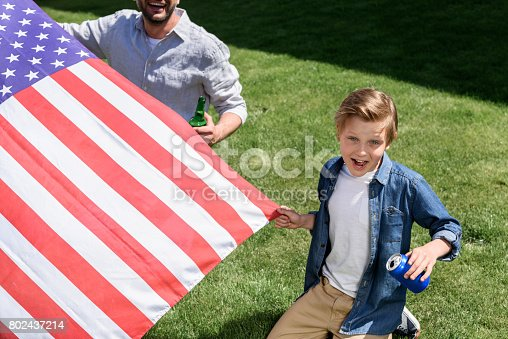 istock father and son sitting on grass with us flag and holding drinks, America's Independence Day concept 802437214