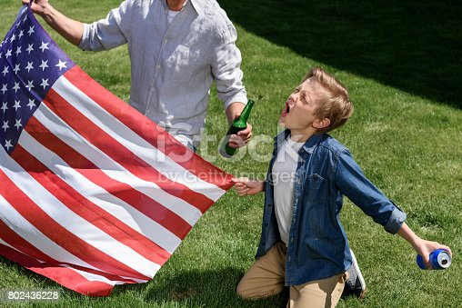 istock father and son sitting on grass with us flag, boy screaming and holding soda can, America's Independence Day concept 802436228