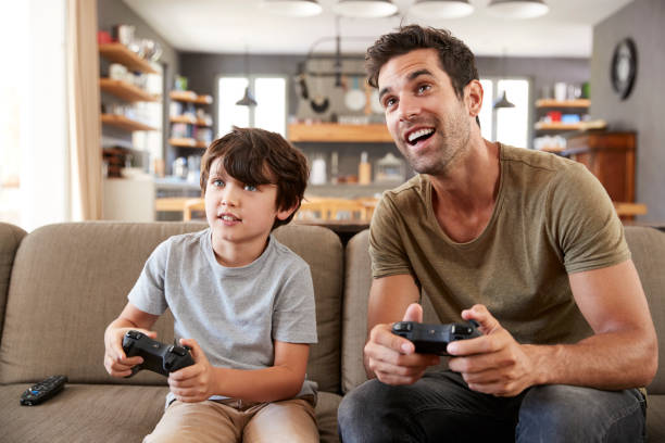 Father And Son Sitting On Sofa In Lounge Playing Video Game stock photo