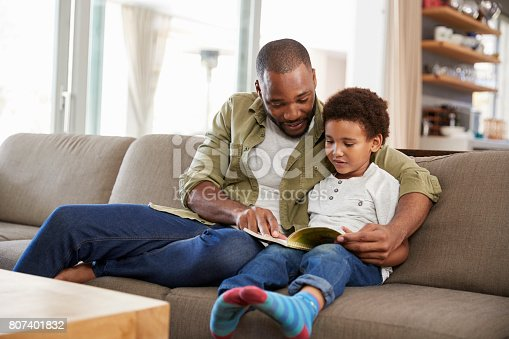 istock Father And Son Sitting On Sofa In Lounge Reading Book Together 807401832