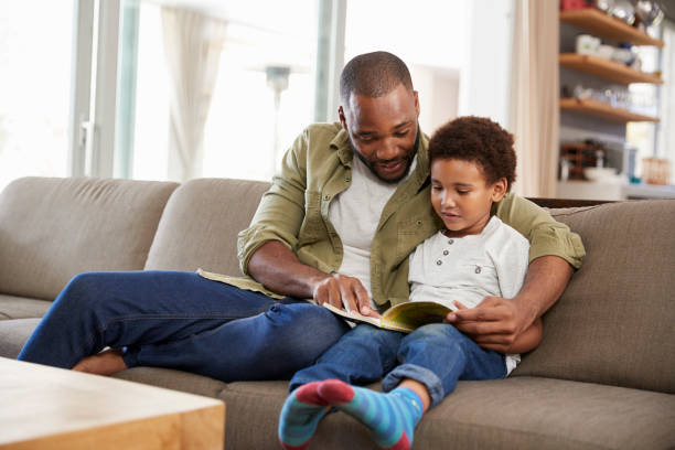Father And Son Sitting On Sofa In Lounge Reading Book Together stock photo