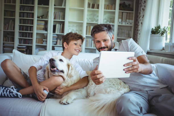 Father and son sitting on sofa with pet dog and using digital tablet picture id652550024?b=1&k=6&m=652550024&s=612x612&w=0&h=n82dtbrepmekssdh3hr 62uvfuh5 se9fqqcdzevdwi=