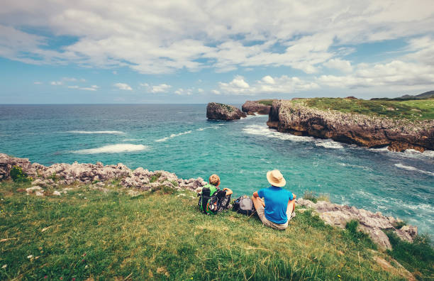 Father and son sitting on the rocky seaside Father and son sitting on the rocky seaside cantabria stock pictures, royalty-free photos & images