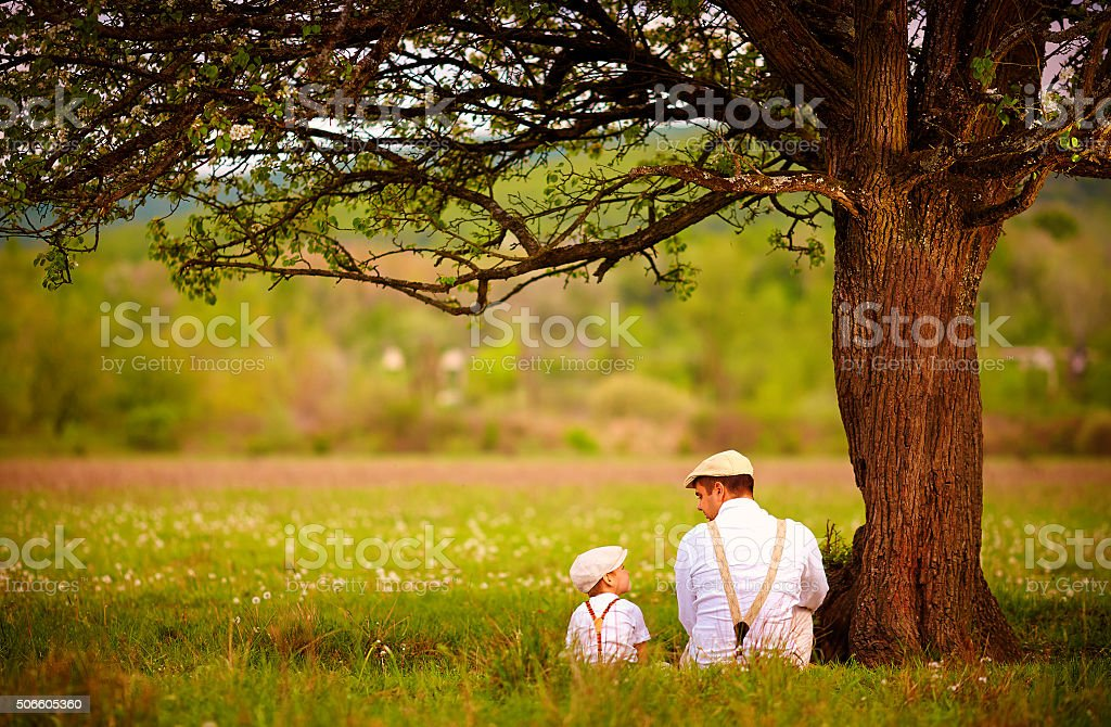 father and son sitting under the tree on spring lawn stock photo
