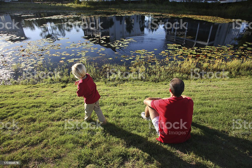 Father and Son Skipping Stones at Lake stock photo
