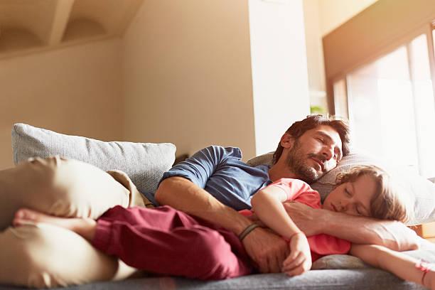 father and son sleeping on sofa - faire un somme photos et images de collection