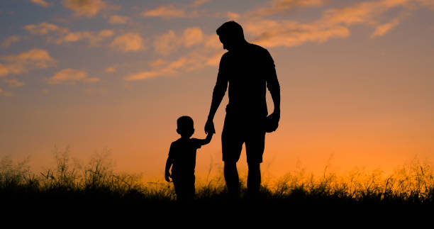 Father and son sling together holding hands. stock photo