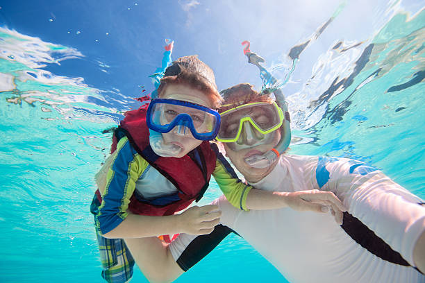 Father and son snorkeling stock photo