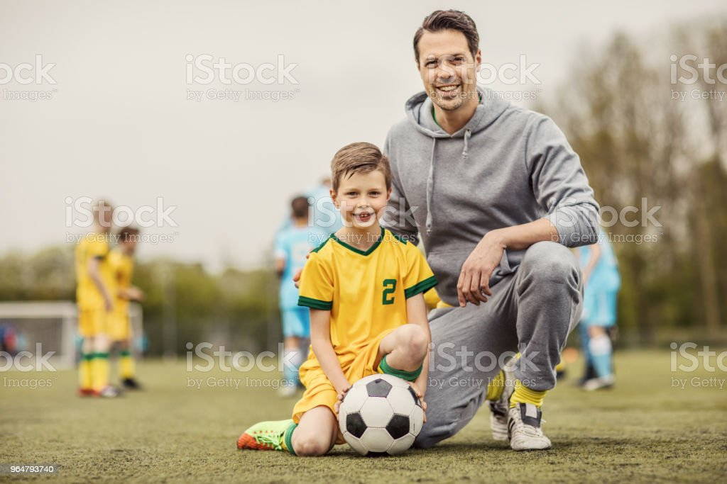 Father and son soccer players posing for photo during a football training session royalty-free stock photo