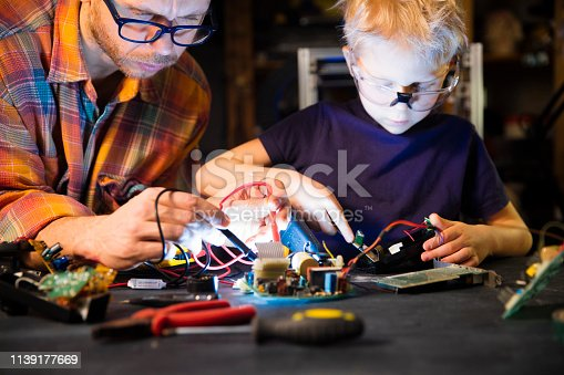 father and son soldering circuit board with soldering iron at home