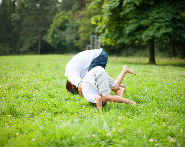 Father and son somersaulting on the ground stock photo