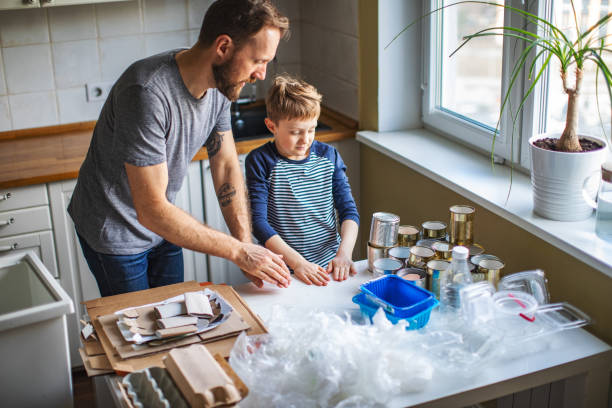 Father and son sorting waste at home stock photo