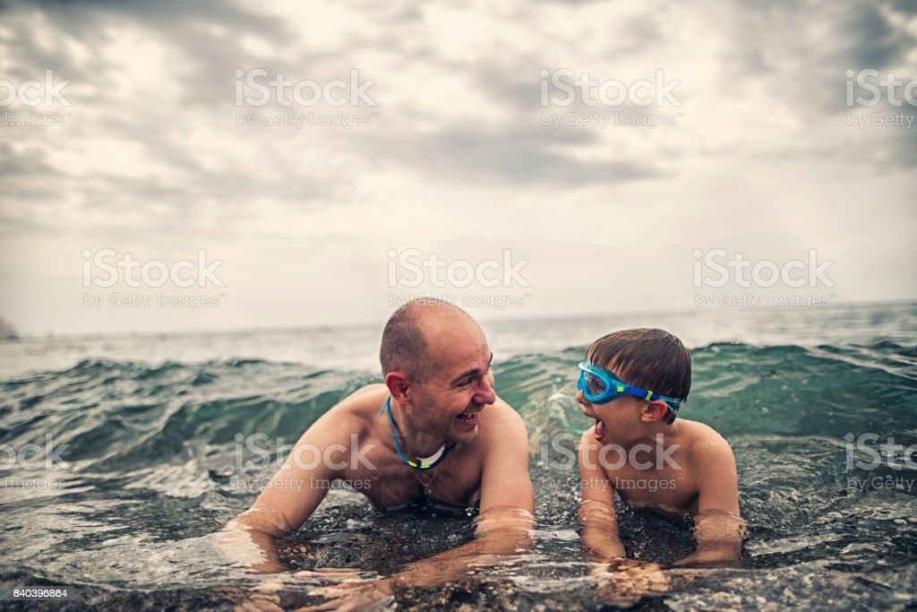 Father and son splashed by sea waves stock photo