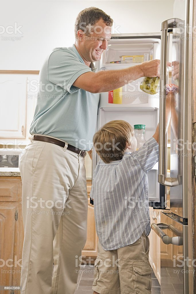 Father and Son Standing in Front of Refrigerator  royalty-free stock photo