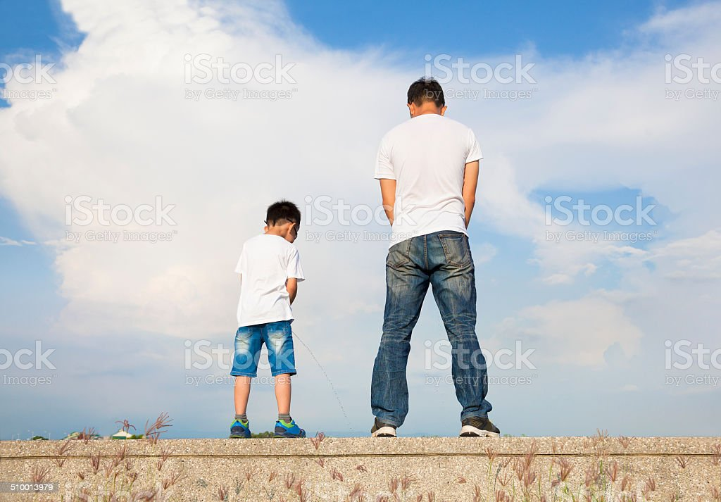 father and son standing on a stone platform and pee together stock photo