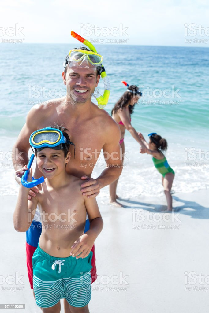 Father and son standing with mother and daughter at beach royalty-free stock photo
