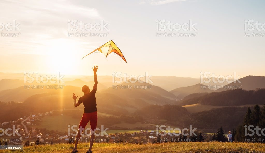 Vater und Sohn beginnen gemeinsam einen Drachen zu fliegen – Foto