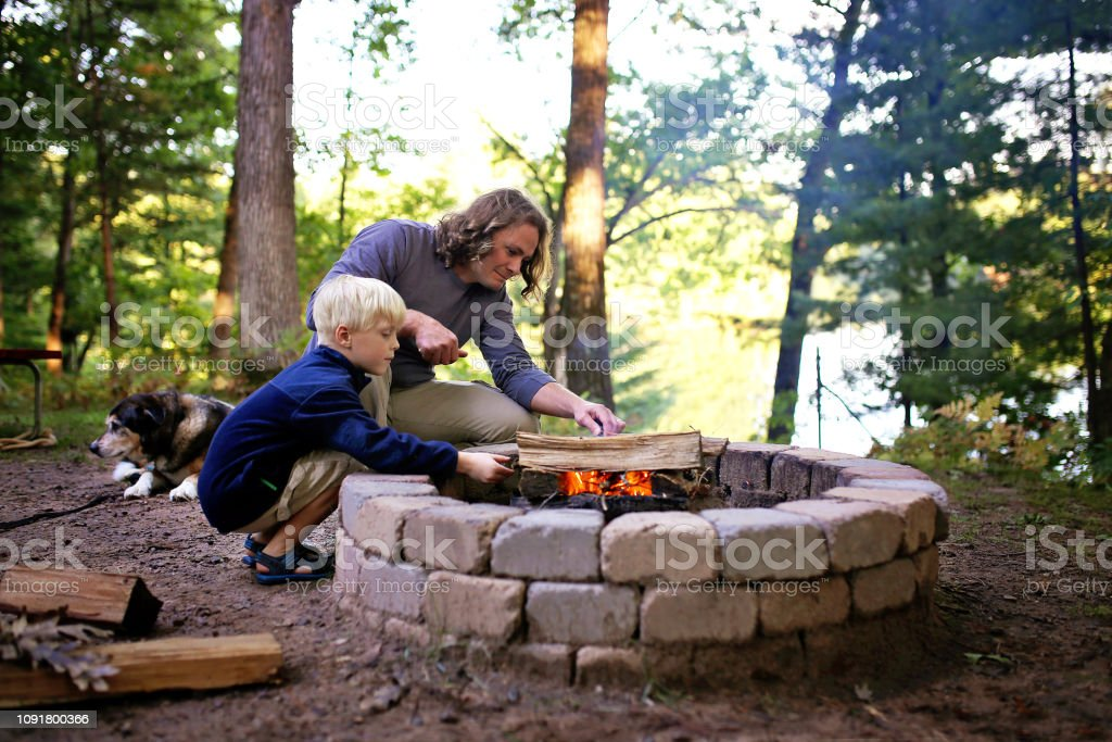 Father and Son Starting Campfire in Fire Ring at Campground Overlooking a Lake in the Woods stock photo