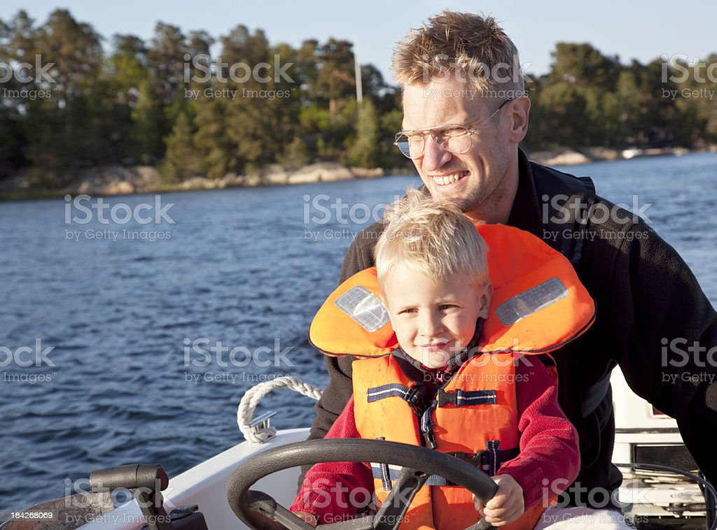 Father and son steering small boat in Stockholm Archipelago royalty-free stock photo