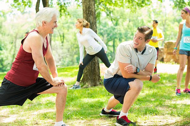 Father and son stretch before 5k race stock photo