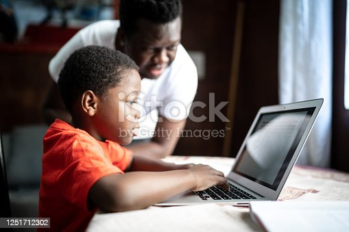 Father and son studying with laptop on a online class at home