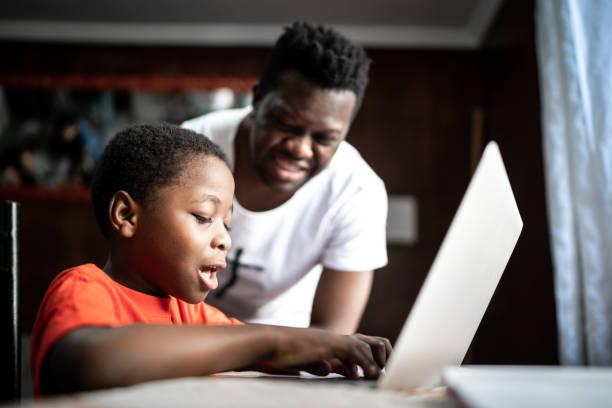 집에서 온라인 수업에서 노트북을 가지고 공부하는 아버지와 아들 - 멀리 떨어진 뉴스 사진 이미지
