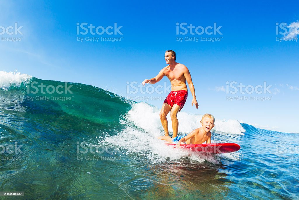 Father and Son Surfing, Riding Wave Together stock photo