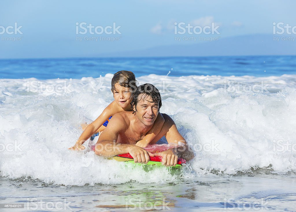 Father and Son Surfing Tandem Togehter Catching Ocean Wave, Care stock photo