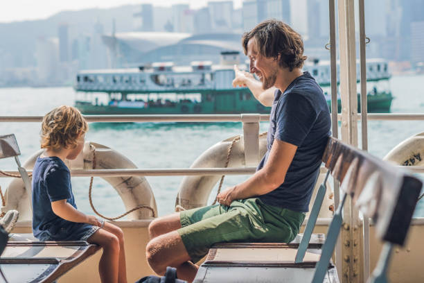 vader en zoon zwemmen met de ferry via victoria-haven in hong kong, china - veerboot stockfoto's en -beelden