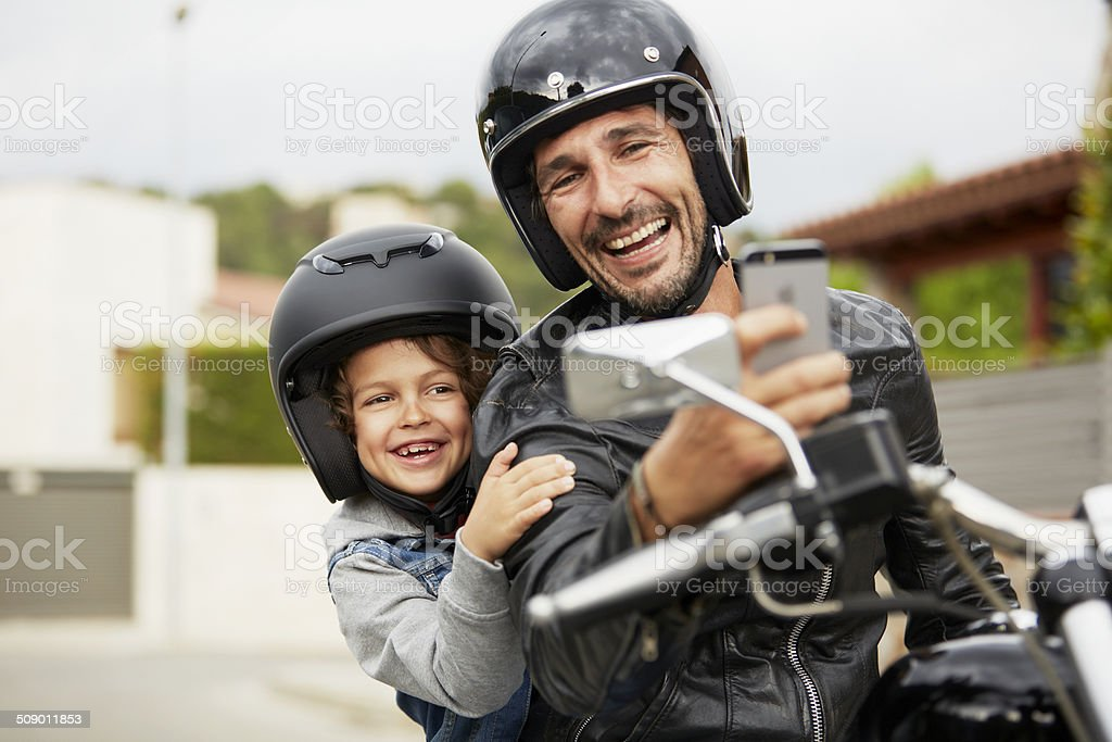 Father and son taking self portrait on motorbike stock photo