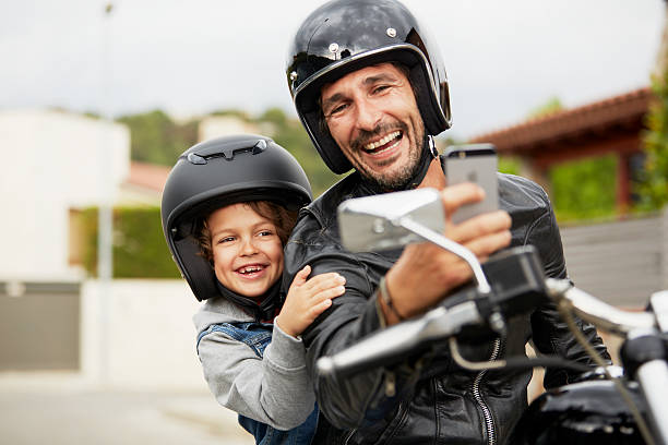 father and son taking self portrait on motorbike - helmet motorbike imagens e fotografias de stock