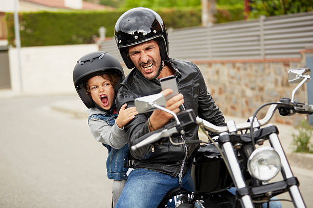 father and son taking self portrait on motorbike - moto sport photos et images de collection