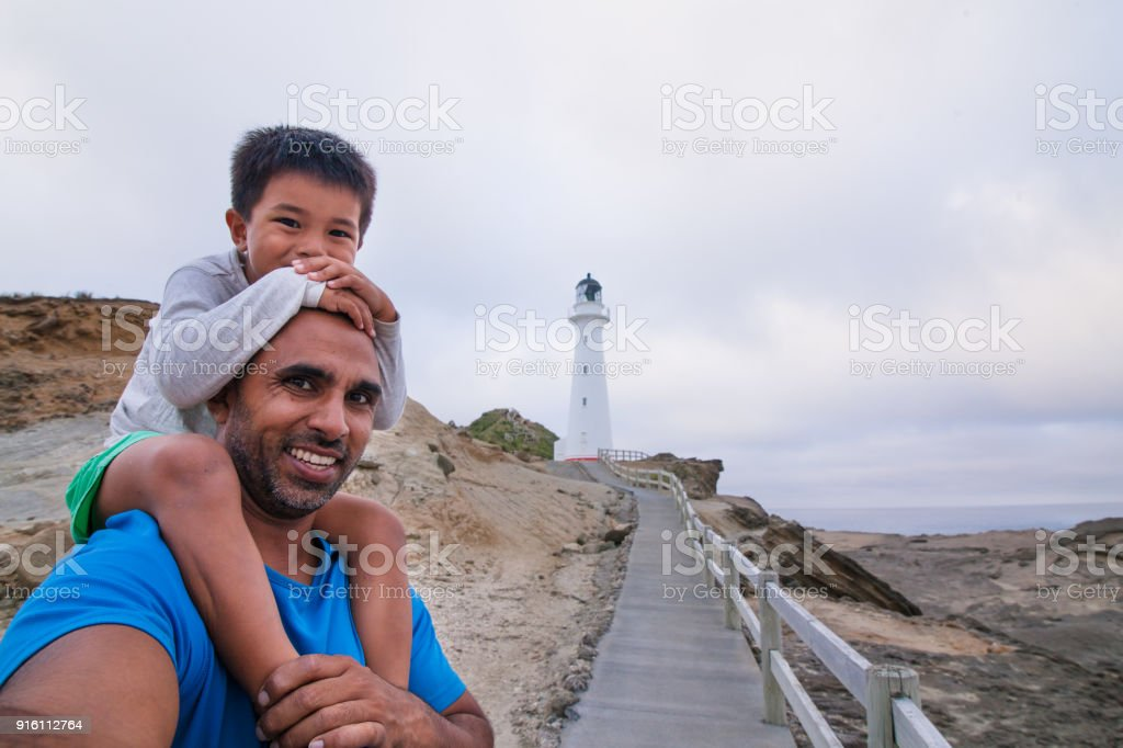 Father and son taking selfie with Castlepoint Lighthouse in background. stock photo