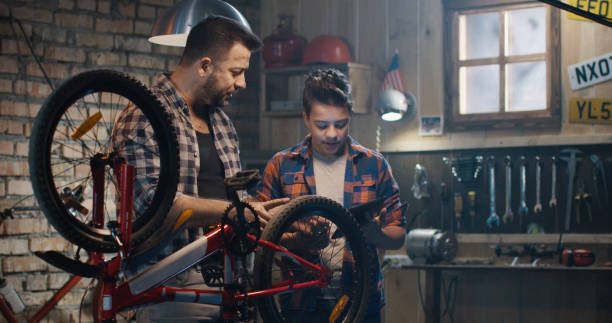 Father and son talking about bike repair Medium shot of father and son talking about bike repair in a garage medium shot stock pictures, royalty-free photos & images
