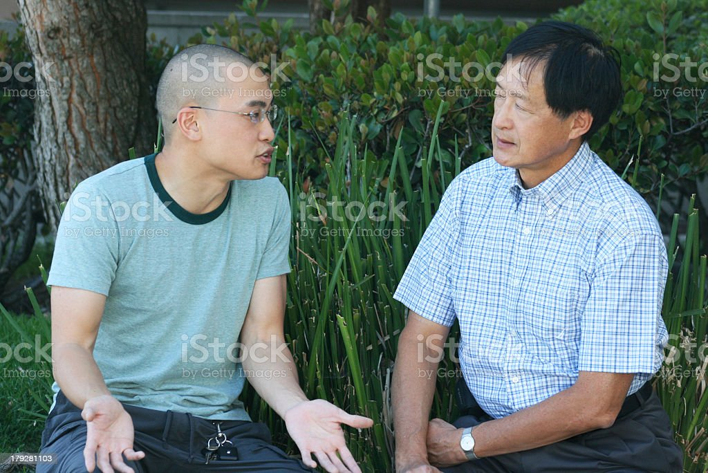 Father and son talking in a garden stock photo