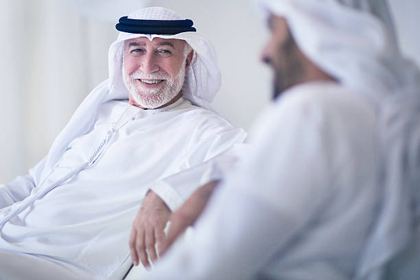 Father and son talking Middle Eastern father and son having a good time talking at home, both wearing the traditional Dishdasha. arabia stock pictures, royalty-free photos & images
