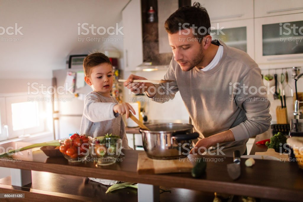 Father and son tasting a soup - foto stock