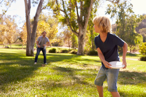 Father And Son Throwing Frisbee In Park Together Father And Son Throwing Frisbee In Park Together plastic disc stock pictures, royalty-free photos & images