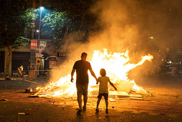 father and son throwing objects at a bonfire, barcelona - petard stock photos and pictures