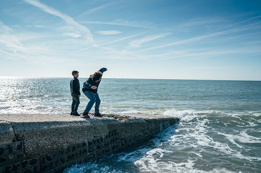 Father and son throwing stones to the ocean