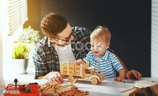 istock father and son toddler gather craft a car out of wood and play 673107574
