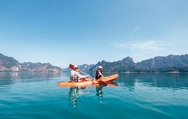 Vater und Sohn paddeln gemeinsam im Kajak auf dem Cheow Lan See in Thailand. Urlaub mit Kindern Konzept Bild. – Foto