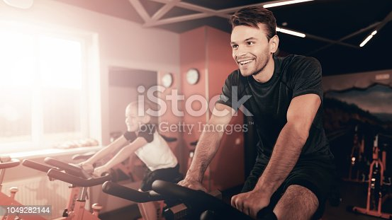 997711042istockphoto Father And Son Training On Bike Trail In The Gym. 1049282144