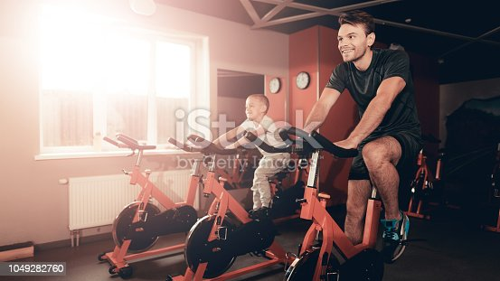 997711042istockphoto Father And Son Training On Bike Trail In The Gym. 1049282760