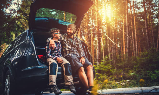 father and son travelling by car - hecktürmodell stock-fotos und bilder